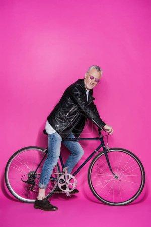 Photo pour Heureux homme haut à la mode, porter la veste en cuir, sunglesses et vélo isolé sur pink - image libre de droit