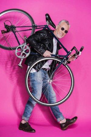 stylish senior man with bicycle