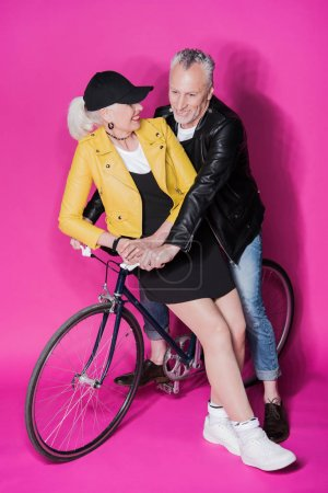 Photo for Smiling stylish senior couple in leather jackets riding bicycle together - Royalty Free Image