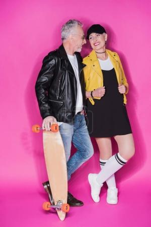 Photo for Handsome senior man with skateboard and stylish beautiful woman standing together isolated on pink - Royalty Free Image