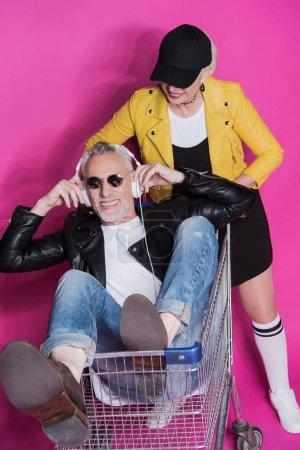 Photo pour Femme senior élégante souriante regardant gai homme senior au casque et lunettes de soleil assis dans le chariot et souriant à la caméra - image libre de droit
