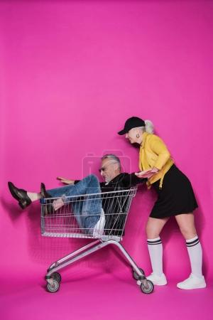 Photo for Side view of smiling stylish senior woman pushing shopping trolley with joyful senior man having fun - Royalty Free Image