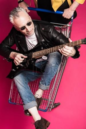 Photo for Handsome senior man in leather jacket and sunglasses sitting in shopping trolley and playing electric guitar - Royalty Free Image