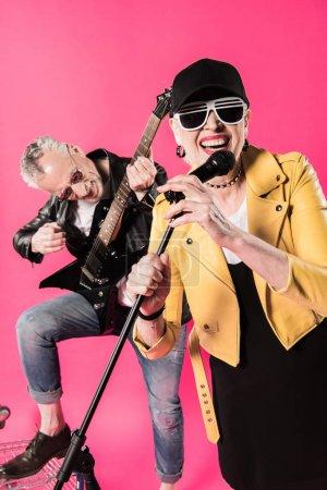 Photo pour Joyeux élégant couple âgé de musiciens de rock and roll isolé sur rose - image libre de droit