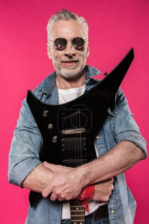 Senior man with electric guitar