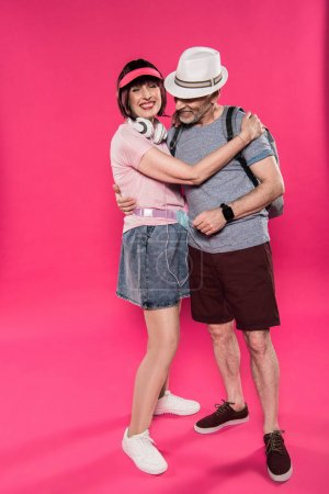 Photo for Stylish cheerful man and woman hugging each other isolated on pink - Royalty Free Image