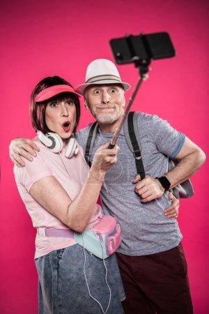 Photo pour Portrait de couple de personnes âgées grimace prenant selfie sur monopode isolé sur rose - image libre de droit