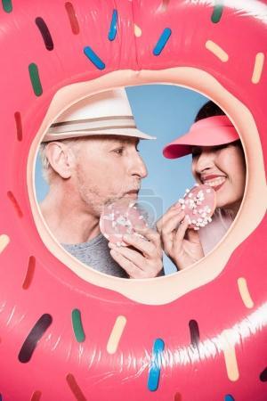 Elderly couple eating sweet doughnuts