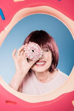Woman holding doughnut in front of eye