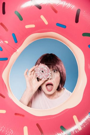 Photo for Woman with facial expression holding doughnut in front of eye into swimming tube - Royalty Free Image
