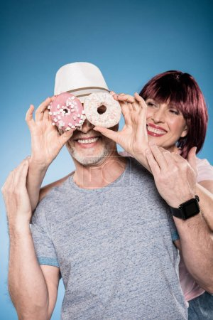 Photo for Carefree elderly couple fooling around with sweet doughnuts - Royalty Free Image