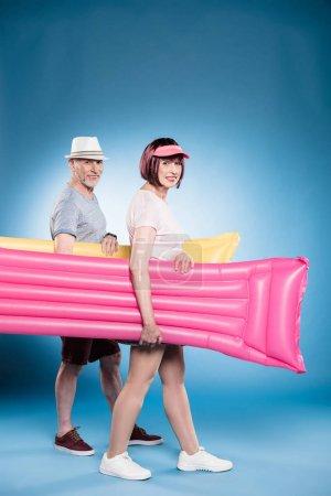 senior couple holding swimming mattresses