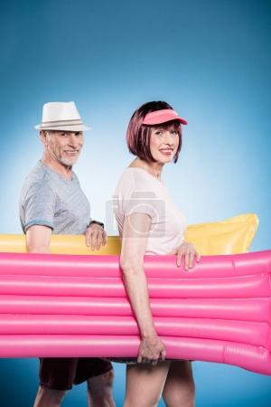senior couple holding swimming mattresses