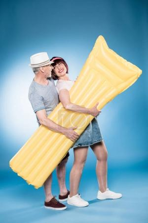 elderly couple holding swimming mattress