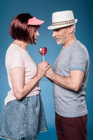 elderly couple holding hands with lollipop