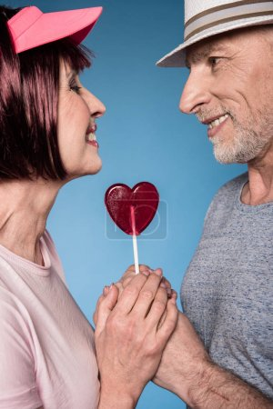 Photo for Stylish elderly couple holding hands with lollipop in form of heart isolated on blue - Royalty Free Image