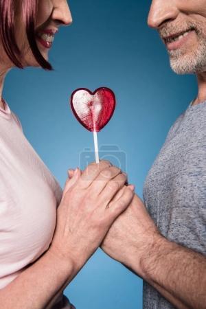 Elderly couple holding hands with lollipop