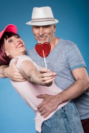 Elderly couple hugging and holding lollipop