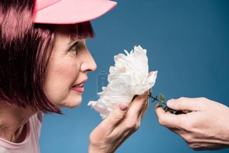 Beautiful elderly woman smelling flower