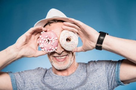 Man holding donuts in front of eyes