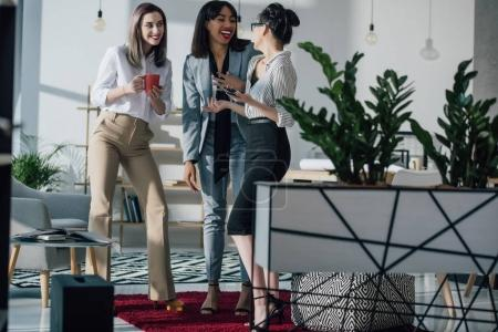 Photo for Smiling young businesswomen standing together and talking at coffee break - Royalty Free Image