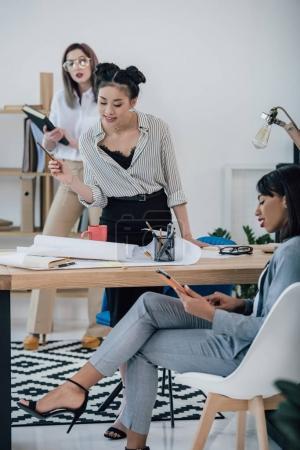 Businesswomen working with blueprint
