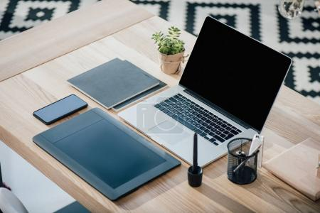 Photo for Close-up view of laptop with blank screen, graphic tablet and smartphone on wooden table - Royalty Free Image