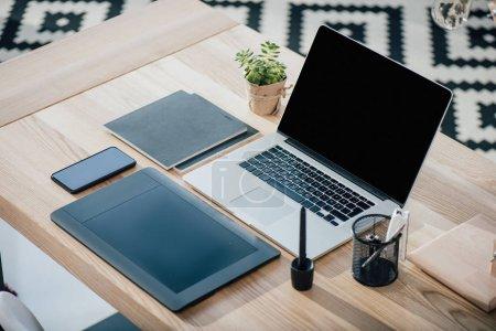 Photo pour Vue rapprochée d'ordinateur portable avec écran blanc, tablette graphique et smartphone sur table en bois - image libre de droit