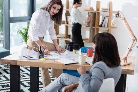Photo pour Femmes d'affaires jeunes professionnels travaillant ensemble dans les bureaux modernes et discuter - image libre de droit