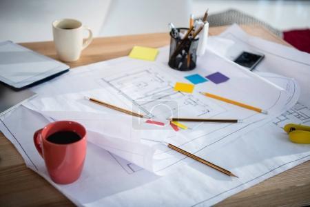 Foto de Vista de primer plano de los planos con suministros de oficina y tazas de café en la mesa - Imagen libre de derechos