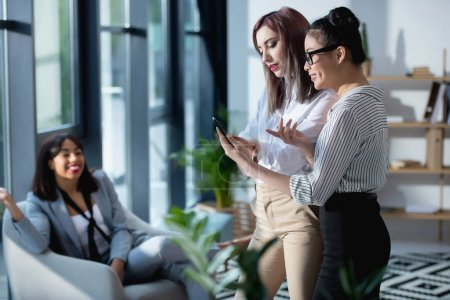 Photo for Young businesswomen standing and using smartphone with colleague sitting behind - Royalty Free Image