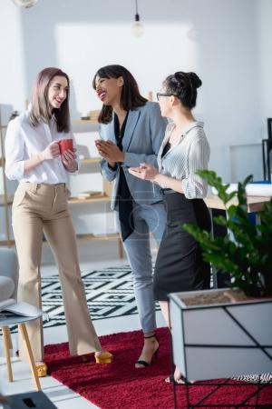 businesswomen drinking coffee and talking at office