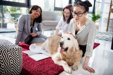 Photo pour Souriantes femmes d'affaires multiethniques caressant chien à fourrure tout en étant assis sur le sol au bureau - image libre de droit