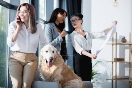 businesswoman talking on smartphone while petting dog