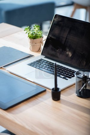 Photo for Close up of laptop with graphics tablet on wooden tabletop at office - Royalty Free Image