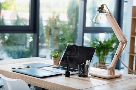 Photo for Laptop with graphics tablet and lamp with office suppliers at workplace - Royalty Free Image