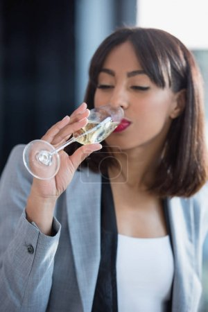 African american businesswoman drinking champagne