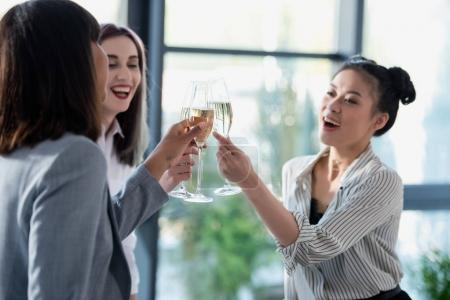 Happy businesswomen clinking with champagne