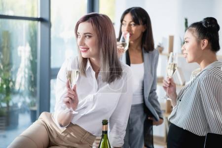 Multiethnic businesswomen drinking champagne
