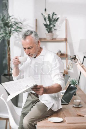 businessman having coffee and reading newspaper