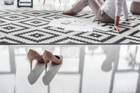 Stilettos on floor and senior businesswoman