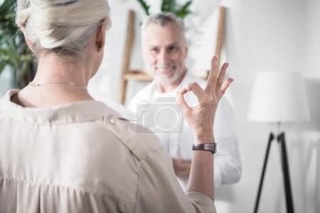 Photo pour Vue arrière du senior femme montrer signe OK à collègue - image libre de droit