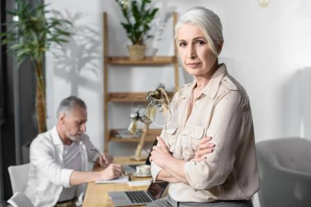 Photo pour Femme d'affaires senior au bureau, collègue masculin sur fond - image libre de droit