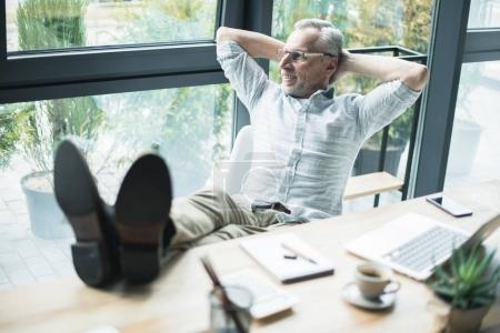 Photo for Senior businessman sitting with his legs on table at office - Royalty Free Image