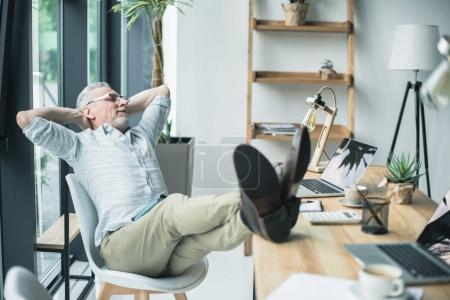 businessman sitting with legs on table