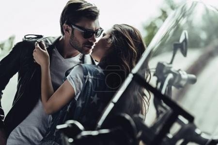 Photo for Beautiful stylish young couple hugging and kissing on motorcycle outdoors - Royalty Free Image