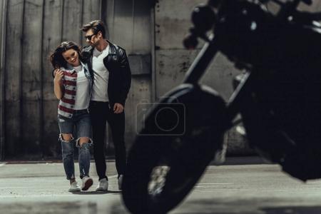 Foto de Elegante joven pareja abrazando a pie junto a la moto de pie al aire libre - Imagen libre de derechos