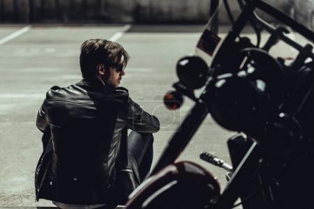 Photo pour Arrière de l'élégant jeune homme en blouson de cuir, assis près de moto et de la recherche. - image libre de droit