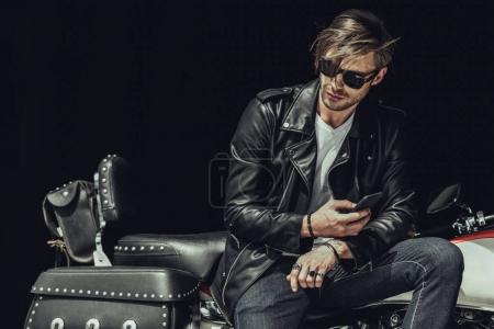 Photo for Stylish young man in sunglasses and leather jacket sitting on motorbike and using smartphone - Royalty Free Image