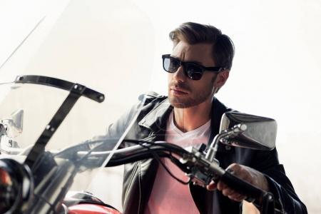 Photo for Handsome stylish young man in sunglasses and leather jacket sitting on motorcycle and looking away - Royalty Free Image